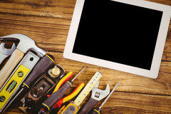 Composite image of tablet pc. Tablet pc against tools on desk Royalty Free Stock Image