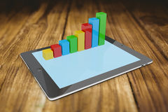 Composite image of tablet pc with graphs. Tablet pc with graphs against wooden table Royalty Free Stock Photos