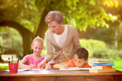 Composite image of teacher helping pupils in library Stock Photography