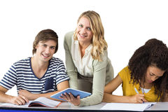 Composite image of teacher helping student in class. Teacher helping student in class against white background with vignette Royalty Free Stock Photos
