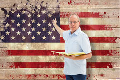 Composite image of teacher holding book and pointing Royalty Free Stock Photos