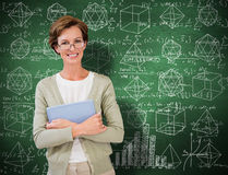 Composite image of teacher holding tablet pc at library. Teacher holding tablet pc at library against green chalkboard royalty free stock photos