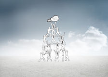 Composite image of team holding up light bulb Royalty Free Stock Photos