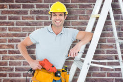 Composite image of technician holding drill machine while leaning on step ladder. Technician holding drill machine while leaning on step ladder against red brick Stock Photos
