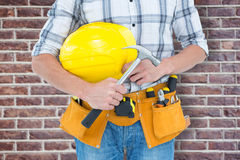 Composite image of technician holding hammer and hard hat Royalty Free Stock Images