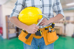 Composite image of technician holding hammer and hard hat Stock Images