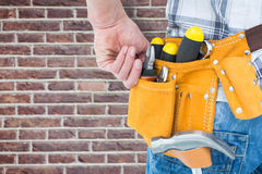 Composite image of technician with tool belt around waist Royalty Free Stock Photos
