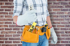 Composite image of technician with tool belt around waist holding pliers Stock Photo