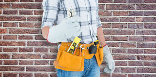 Composite image of technician with tool belt around waist holding pliers Royalty Free Stock Photo