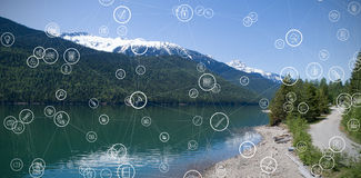 Composite image of technology icons. Technology icons against snowcapped mountain range by river with reflection against sky Stock Images