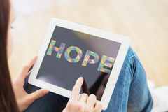 Composite image of teen using a tablet pc sitting on the floor. Teen using a tablet pc sitting on the floor against autism message of hope Stock Images