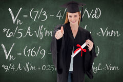 Composite image of teenage girl celebrating graduation with thumbs up Stock Image