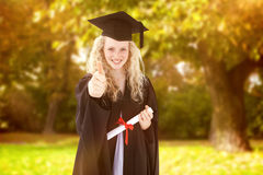Composite image of teenage girl celebrating graduation with thumbs up Royalty Free Stock Image