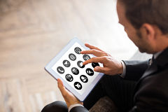 Composite image of telephone with apps icon. Telephone with apps icon  against businessman using tablet Royalty Free Stock Images