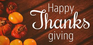 Composite image of thanksgiving greeting text. Thanksgiving greeting text against close up of candies with small pumpkins on table Stock Photos