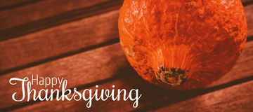 Composite image of thanksgiving greeting text. Thanksgiving greeting text against close up of squash on table during halloween Stock Image
