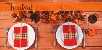 Composite image of thanksgiving greeting text. Thanksgiving greeting text against 2 seats on wood table for christmas dinner Royalty Free Stock Photos
