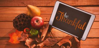 Composite image of thanksgiving greeting text. Thanksgiving greeting text against touch pad on leaf on wood table Stock Image