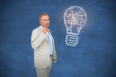 Composite image of thinking businessman. Thinking businessman against blue chalkboard Royalty Free Stock Images