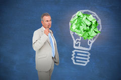 Composite image of thinking businessman. Thinking businessman against blue chalkboard stock photos