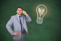 Composite image of thinking businessman. Thinking businessman against green chalkboard stock images
