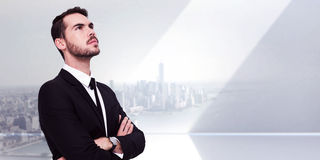 Composite image of thinking businessman with his arms crossed Stock Photo