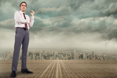 Composite image of thinking businessman holding pen Stock Images