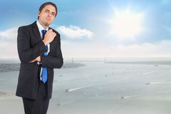 Composite image of thinking businessman holding pen Royalty Free Stock Image
