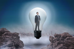 Composite image of thinking businessman in light bulb. Thinking businessman in light bulb against rocky landscape Stock Images