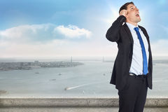Composite image of thinking businessman scratching head. Thinking businessman scratching head against balcony overlooking city Royalty Free Stock Images