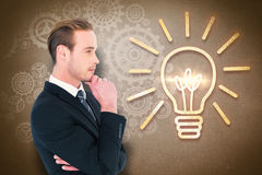 Composite image of thinking businessman standing with hand on chin Royalty Free Stock Image