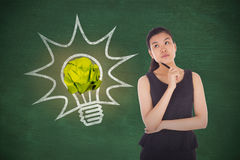 Composite image of thinking businesswoman. Thinking businesswoman against green chalkboard royalty free stock photo