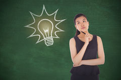 Composite image of thinking businesswoman. Thinking businesswoman against green chalkboard stock images