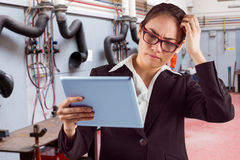 Composite image of thinking businesswoman looking at tablet pc. Thinking businesswoman looking at tablet pc against various eqipments on table in factory Stock Photo