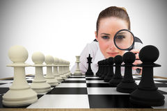 Composite image of thinking businesswoman with magnifying glass Royalty Free Stock Photo