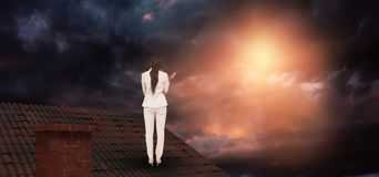 Composite image of thinking businesswoman. Thinking businesswoman against gloomy sky stock photography