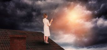 Composite image of thinking businesswoman. Thinking businesswoman against gloomy sky royalty free stock photo