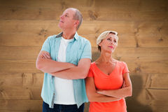 Composite image of thinking older couple with arms crossed Royalty Free Stock Photography