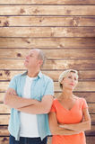 Composite image of thinking older couple with arms crossed Stock Photo