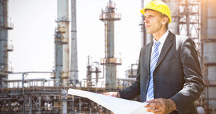 Composite image of thoughtful architect holding blueprint. Thoughtful architect holding blueprint  against view of industry Royalty Free Stock Image