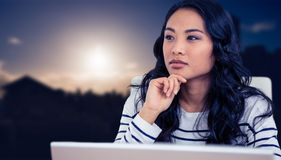 Composite image of thoughtful asian woman with finger on chin Stock Images