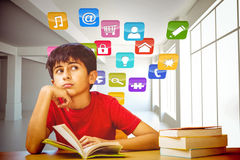 Composite image of thoughtful boy reading book in library Royalty Free Stock Images