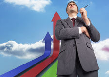 Composite image of thoughtful businessman holding pen. Thoughtful businessman holding pen against colourful arrows pointing up against sky Royalty Free Stock Photo