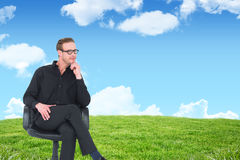 Composite image of thoughtful businessman sitting on a swivel chair. Thoughtful businessman sitting on a swivel chair against blue sky over green field Royalty Free Stock Image