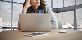 Composite image of thoughtful businesswoman looking away while sitting with laptop at desk royalty free stock images