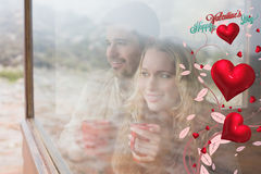 Composite image of thoughtful content couple with cups looking through window Royalty Free Stock Photography