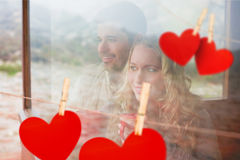 Composite image of thoughtful content couple with cups looking through window Stock Photo