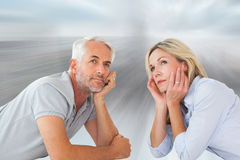 Composite image of thoughtful couple lying and looking up Royalty Free Stock Images