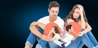 Composite image of thoughtful couple sitting on floor back to back Royalty Free Stock Photo