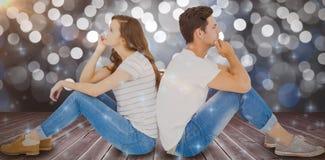 Composite image of thoughtful couple sitting on floor back to back. Thoughtful couple sitting on floor back to back against glowing background Royalty Free Stock Photo